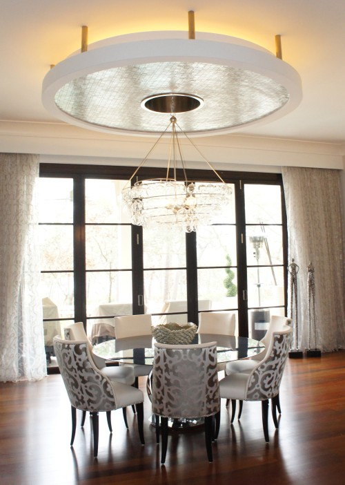"In the Dining area, there is a round disc suspended from stainless bars, with recessed glowing lights.  It appears to hover over our 72"" dining table.  The chairs bring in some warmth with its leather seats and gray printed Romo fabric outbacks."