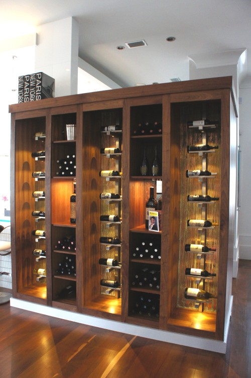 This wine storage and display area was custom designed to serve, not only as functional storage, but also a clever way to separate the Kitchen from the Entry, without feeling closed off.  The warmth of the wood and the accent lights radiates out into the room.