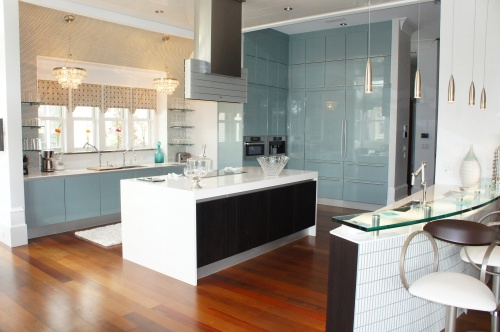 Here you can see how beautifully the Ipe wood floors contrast with the coolness of the Poggen Pohl blue glossy cabinets.  Notice the island, with its white countertop waterfalling down the sides for a modern and lightening effect.