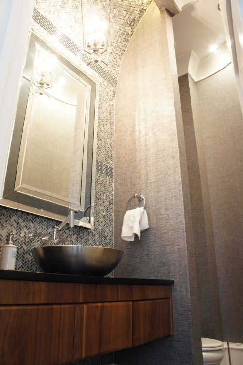 This Powder Bathroom has custom floating cabinet, black granite counter top, glass backsplash and accent pendant light.