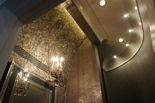 The top of this vanity wall curves out and ends in a recessed cove that lights up the wall tile and shows off the architecture.
