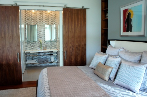 Solid wood sliding barn doors separate the bedroom and bath.