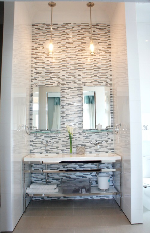 "This polished nickel double vanity fit perfectly in this space!  The reflective White Ice walls, horizontal staggered glass and marble tile, and polished metal all twinkle from the lights of the two fabulous ""Caviar"" pendants by Arteriors.  The mirror/shelves are by Waterworks."