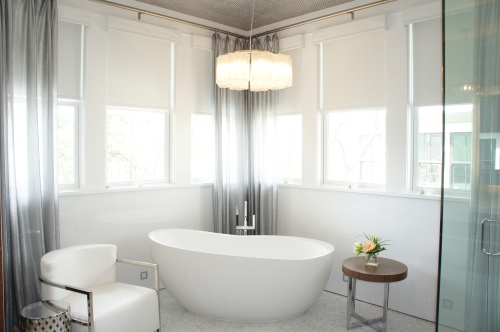 White Ice slab walls, a Waterworks tub, reflective Carrera marble mosaic floors and accents of silver!  Turned out beautiful!