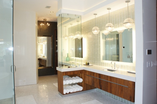 "The Vanities consist of custom floating cabinets, shimmering glass ""waterafalling"" tiles, backlit mirrors, and a floating fireplace!"