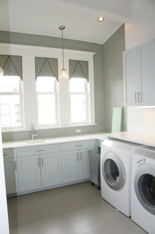 Laundry rooms usually get the cold shoulder in most houses I encounter, but this one is definitely different!  The walls are treated with penny round Ann Sacks tiles with slight gray-blue rims.  The slight color creates a gray color contrast for the walls that looks great against the white trim and pale gray cabinets.  Accent pendant lights add to the charm.  This is the perfect little coastal modern laundry room!