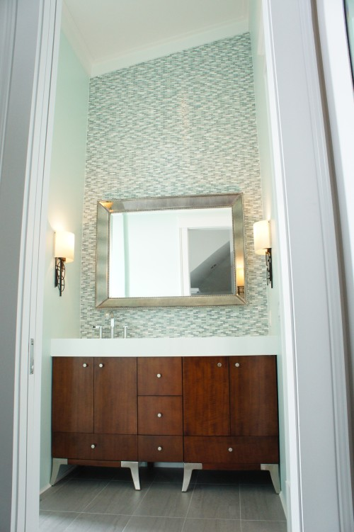 Both girls' rooms have the same bathroom design, except they are mirror images of each other.  The vanity is a furniture piece that we added a thick solid surface top to so that it looked built-in.  We laid the Bliss stone and glass mosaic tiles all along the backsplash, all the way up to the vaulted ceiling.