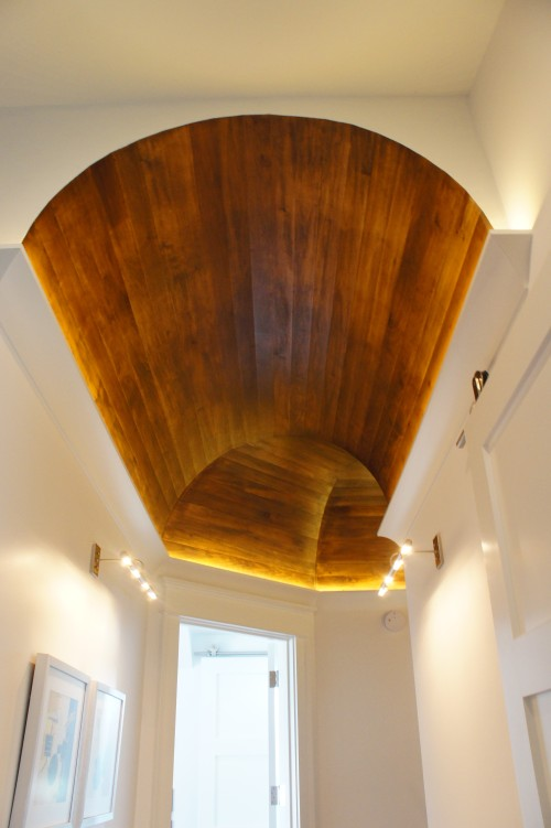 "The hallway ceiling on the third floor was a barrel vault, with stained wood for warmth against all the white.  The crown molding hides cove lighting that accents this architectural detail.  This is yet another very cool way the ceilings were shown some ""love"" on this project!"