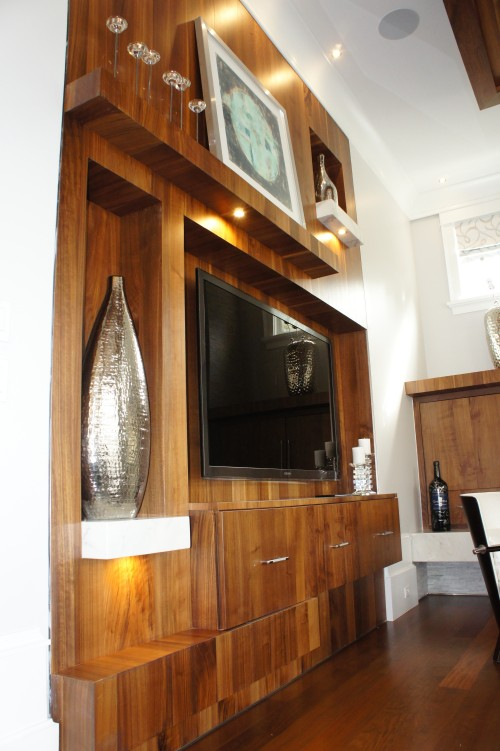 I designed this media wall to be asymmetrical, with mantle, shelves and t.v. console at varying depths.  It is made from quarter sawn maple in a walnut finish.  Instead of trying to make the t.v. the focal point, we succeeded in making that whole area a large sculptural feature.