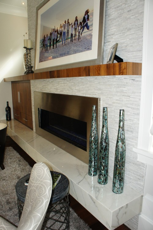 The fireplace surround is covered in horizontal pieces of Carrera marble with varying depths and alternating polished and tumbled finishes.  The hearth is made from slabs of Carrera marble.  This white helped balance all the wood tones in the room.