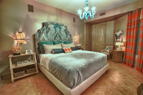 This guest room was furnished with a tall bed, upholstered in a gorgeous Schumacher fabric. Bedside shelves and apricot beaded sconces finish off the bed wall.