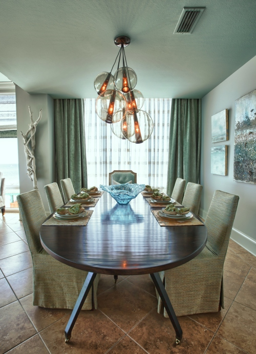 The side chairs are slipcovered in a green textured linen, and the host chairs are upholstered in a fresh pale aqua leather! The drapes and sheers give this area intimacy and drama!