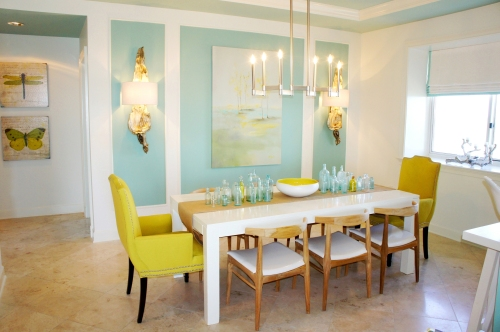 My white lacquer parsons table allowed the vibrant colors around it to stand out.  The dining chairs are raw teak, with white patent vinyl seats.  I covered the host chairs by C.R. Laine in an exciting shade of chartreuse, which was supported in the artwork and bowl centerpiece!