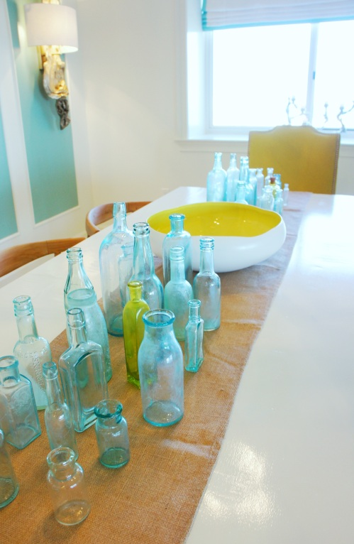 For my centerpiece, like many other details in this condo, I decided to go big or go home!  For a vibrant color pop, I found a lot of antique glass bottles and congregated them on my burlap table runner.  When entertaining, these bottles would look beautiful with the occasional daisy , and the bowl would look great with floating candles!