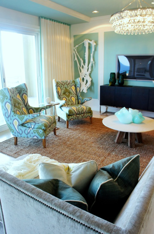 I accented all the heavier upholstery with these two contemporary wing chairs.  I absolutely love these chairs!  They are so comfortable, too!  I chose a colorful Ikat print that pulls together the blue, green and yellow I've used throughout the unit. You can also see here what a great vantage point a person lounging on the chaise lounge will have, with a view of the beach, the television, the goings-on in the kitchen, and the other living room seating.