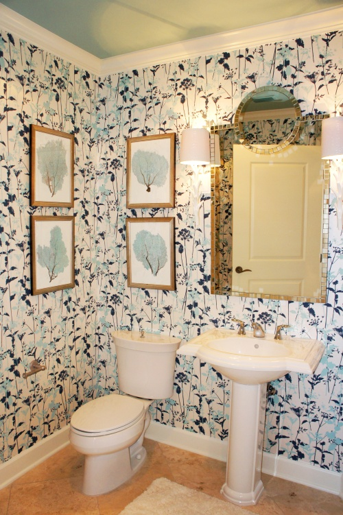 I jazzed up this small bathroom by papering the walls in this fun, blue and white wallcovering and hanging a chic mirror above the pedestal sink.  I flanked the mirror with two white coral Regina  Andrews sconces.