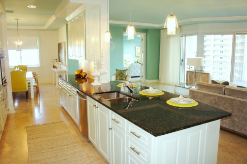 Painting the cabinets a pale ice blue brightened the kitchen and created pleasing contrast with the black granite countertops.  I replaced all the bronze knobs with stainless contemporary knobs and pulls for a fresher look.