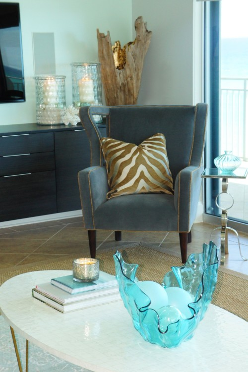 This corner is cozy with its Century Furniture contemporary wing chair, covered in a charcoal velvet and shimmering gold linen welt.  The gold velvet zebra pillow and glowing gold of the driftwood sculpture, along with the candle light radiate nicely out from all the gray and green.
