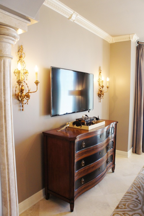 "This beautiful Henredon chest added some warm woods to the room. I flanked the t.v. with some gold-leafed Currey and Company sconces to add some needed extra light and provide some extra ""jewelry"" to the room."