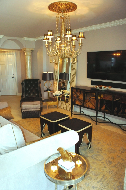 I replaced the chandelier with a larger, more elegant gold wood chandelier, with brown silk shades.  The glass front of the t.v. console has a gold hue of its own, that blends nicely with all the colors.