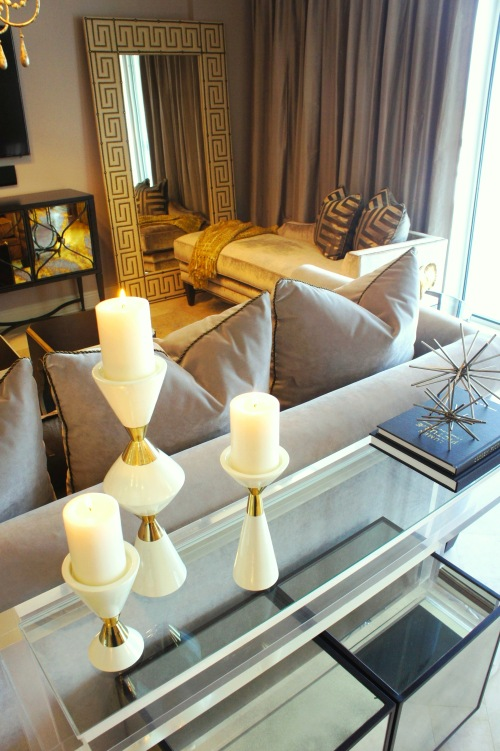 The corner of the room was best furnished with a luxurious Century chaise lounge, covered in velvet! The fretwork pillows tie in the greek key pattern in the mirrors.  To help balance the gold of the wool Oushak rug and accents, I covered the sofa in a plush, matte gray velvet. Behind the sofa, I chose to use a glass and acrylic sofa table that added a modern touch, while remaining simple enough to not take away from the lines of the sofa.