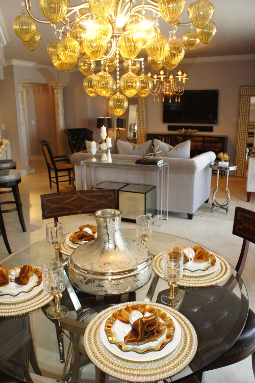 I furnished the dining area with an industrial pedestal table by Drexel Heritage, then added some side chairs with wood inlay.  The large, gold Murano glass chandelier added some drama that helped provide weight to this area.
