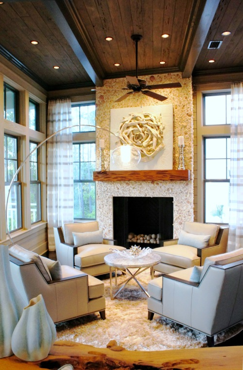 The long layout of this room called for a second seating area--one that enjoys the fireplace, and promotes conversation. The modern gray leather club chairs are centered around a round, Century Furniture mother of pearl table.  The floor lamp has an exaggerated arch that allows the light to be centered over the arrangement, while not taking away from the view, or the lines of the room.
