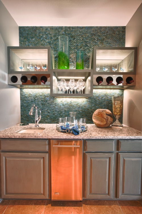 We did a partial demo of the Wet Bar to remove the generic upper cabinets.  We designed this contemporary wine glass and bottle storage system at alternating heights, then added some up-and down-lighting that accents the sleek glass tile.