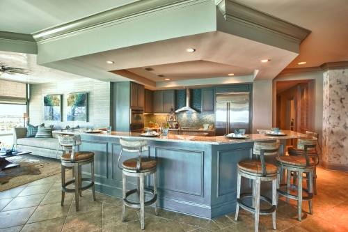 In this kitchen makeover, we provided new countertops, finished the cabinets in a distressed warm gray, added some paneling to the bar front and livened the backsplash with new tile.