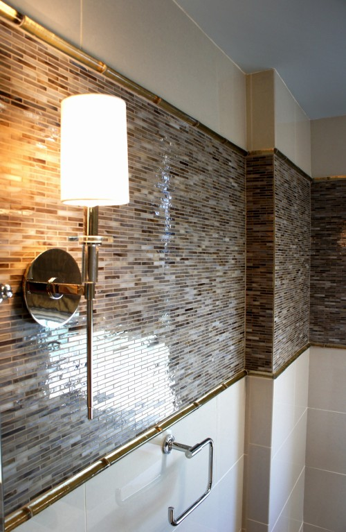 The horizontal band of tile is transitioned into the sleek porcelain tile with some taupe glass pencil trim.
