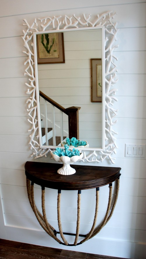 Floating rope console and coral mirror set the tone for the rest of the house: Casual, whimsical, bright and fun.