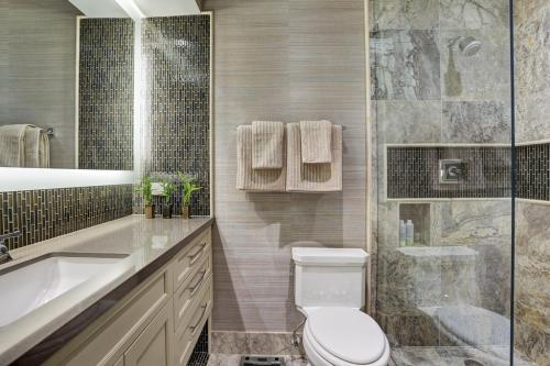 HIS Bathroom AFTER:  Whoa, what a difference, right??  Clean lines, masculine, bright, functional.  The electric mirror provided beautiful bright ligh, which reflected off of the glass tiles on the backsplash.  textured grasscloth stand up to the warm colors and finishes in this bath.